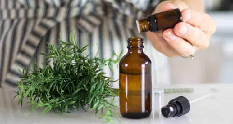 hand dropping essential oils into spray bottle