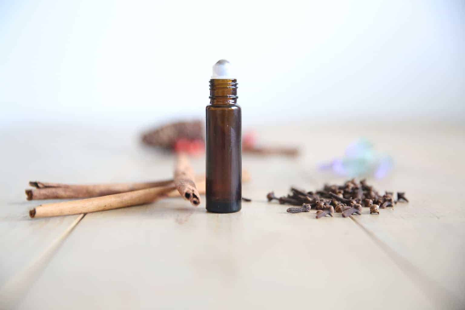 homemade floral scented women's rollerball perfume surrounded by cinnamon sticks
