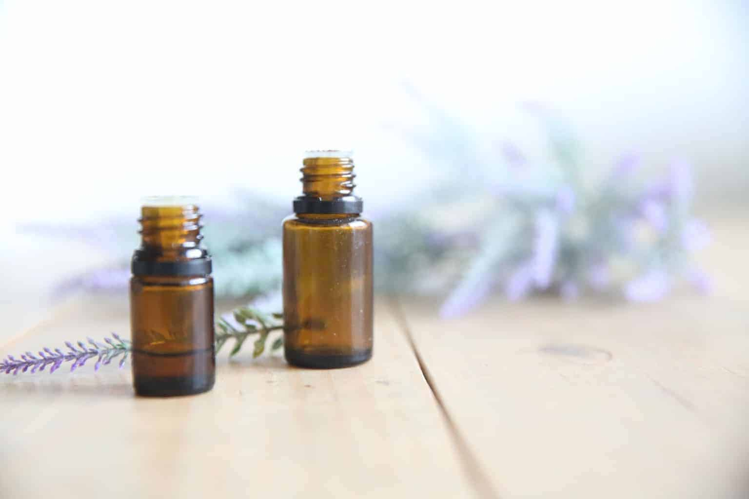 lavender essential oil dropper bottles surrounded by dried lavender sprigs