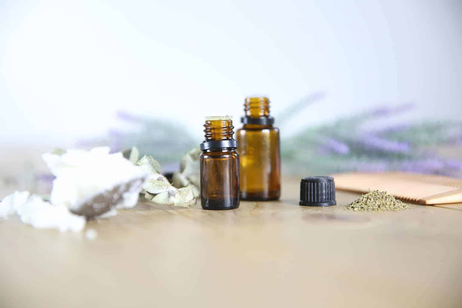 essential oil bottles with lavender sprigs on wooden table