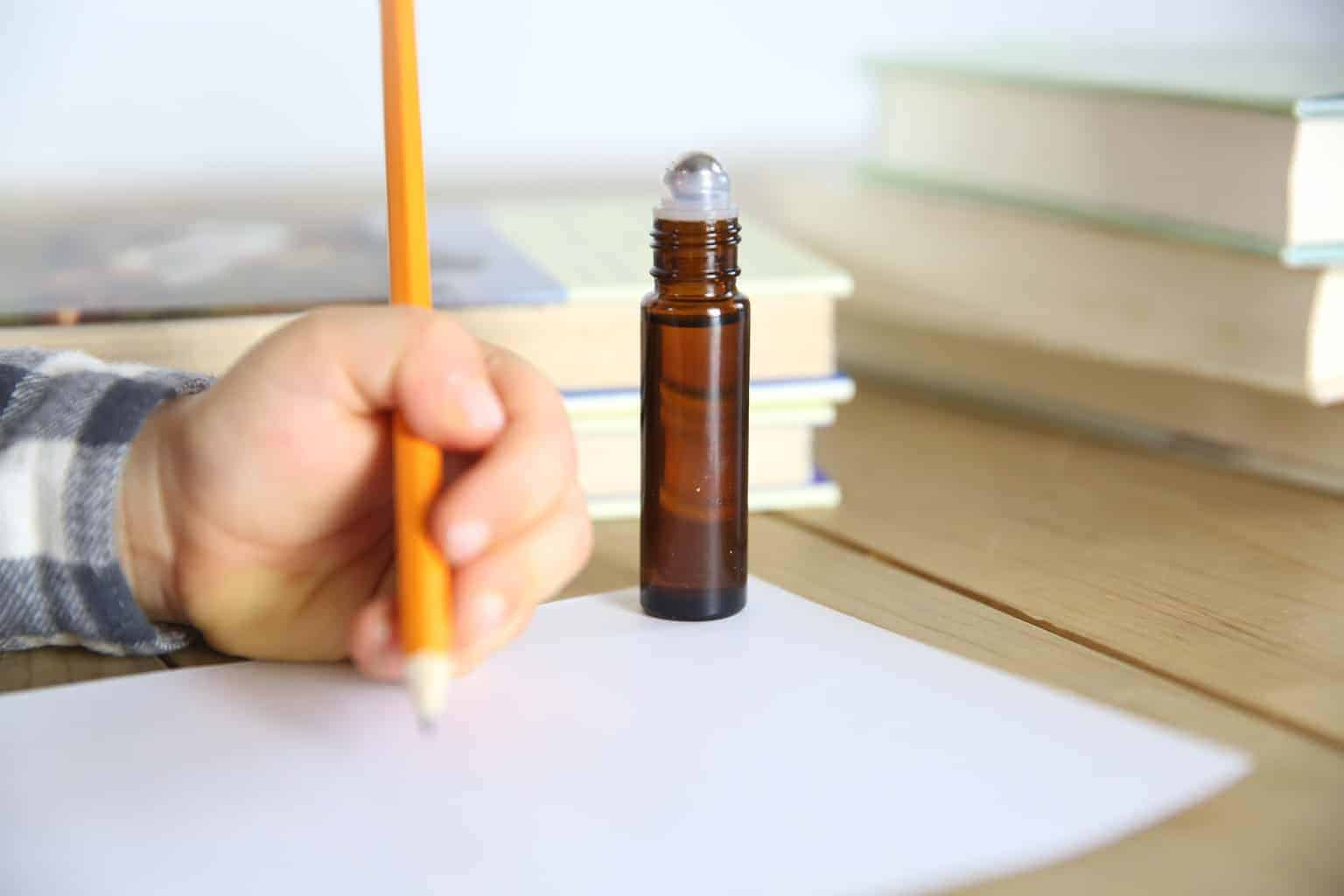 little kid studying with essential oil roller bottle for focus and concentration on table