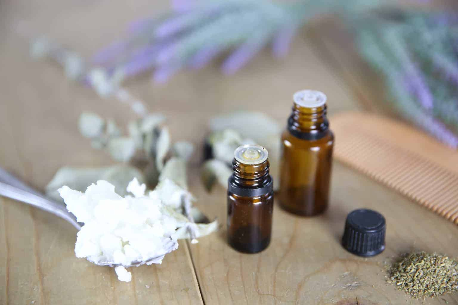 essential oil dropper bottles and coconut oil on metal spoon