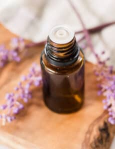 Overhead shot of lavender essential oil bottle and lavender sprigs.
