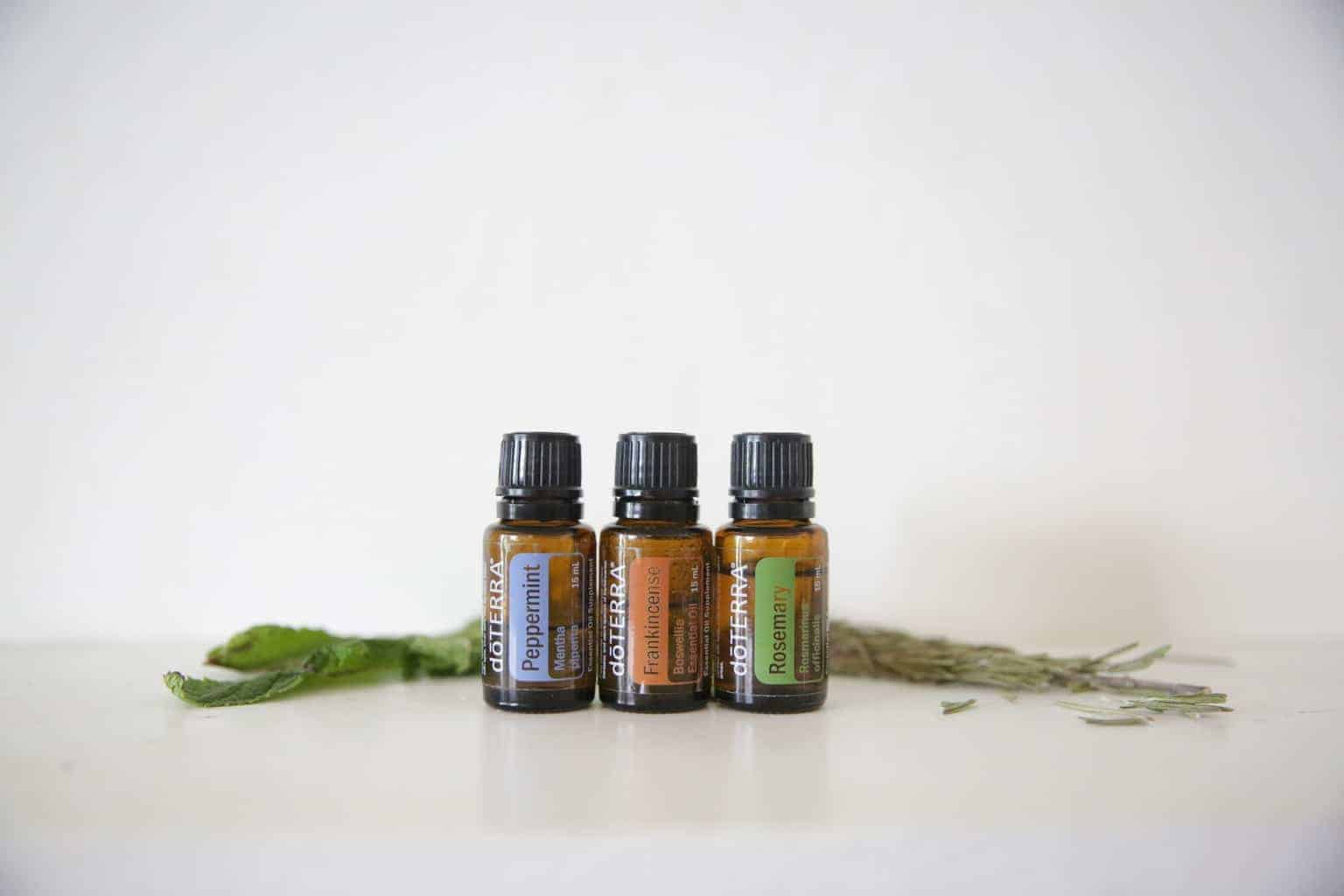 essential oil bottles with rosemary leaves