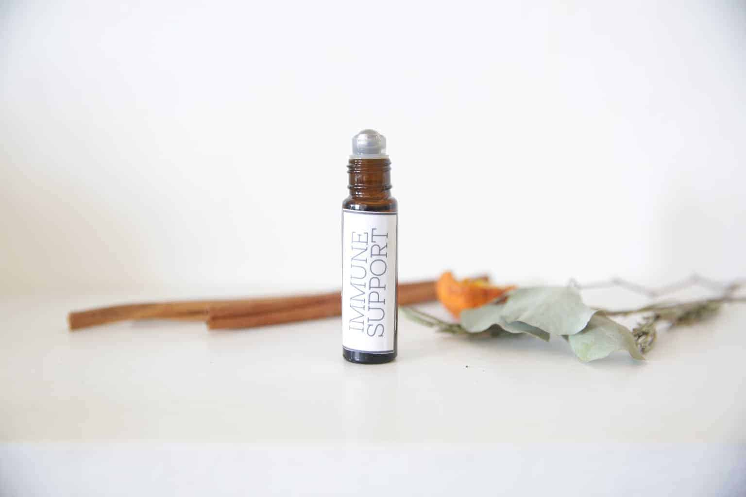 IMMUNE SUPPORT ROLLERBALL BOTTLE WITH CINNAMON STICKS ON WHITE MARBLE