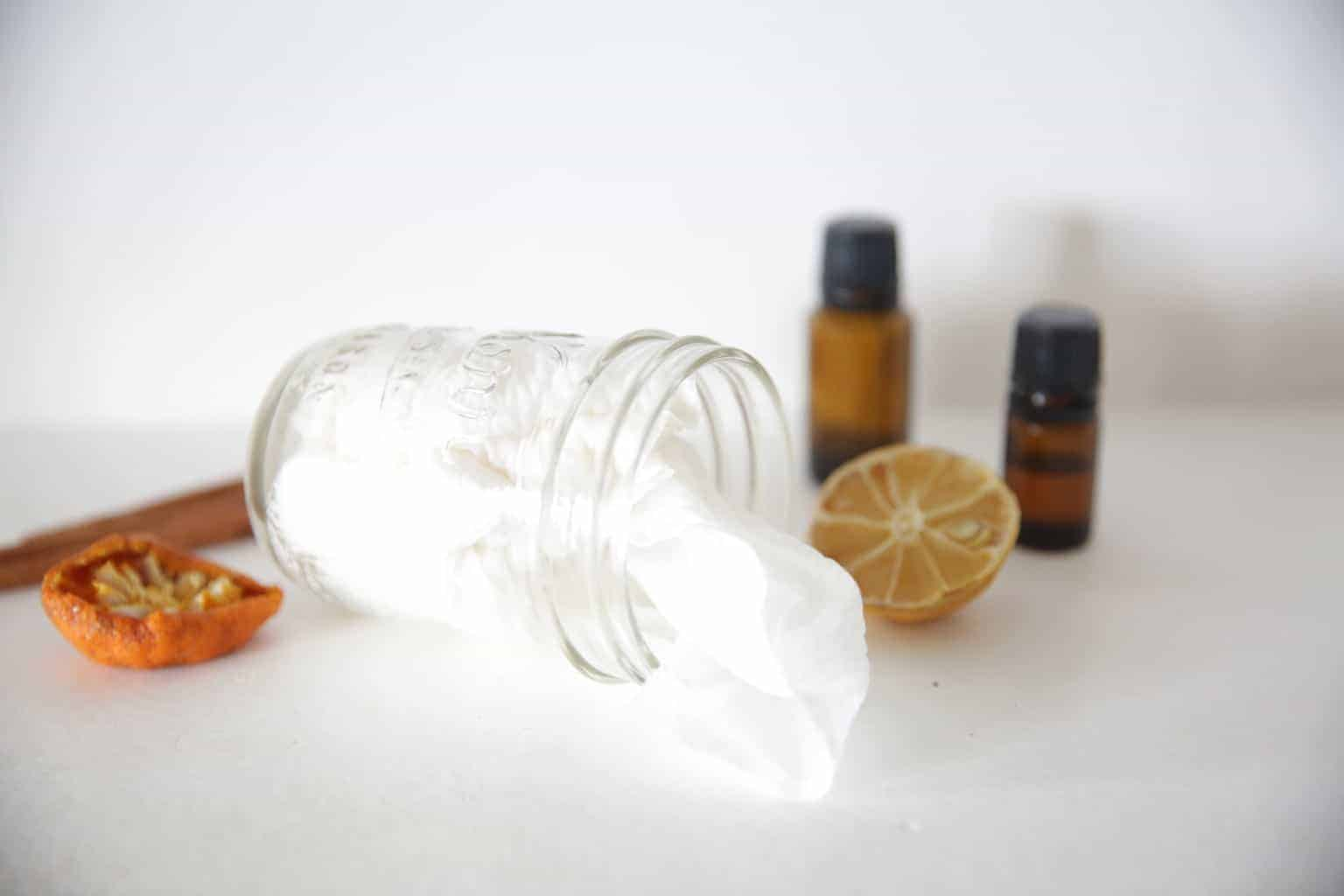 small glass jar with homemade cleaning wipes on its side with dried lemon and orange slices