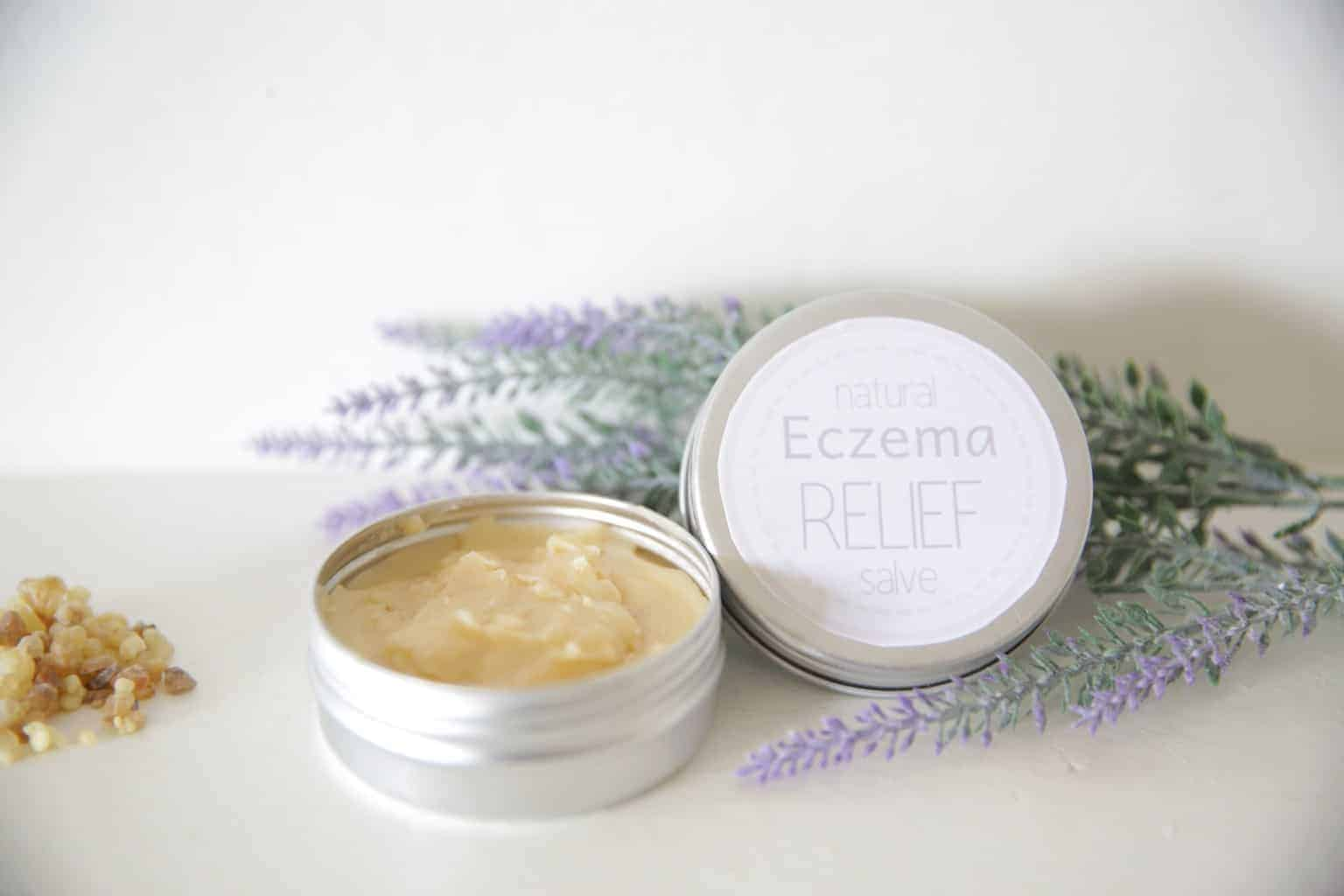 homemade healing salve in small metal container with lavender springs