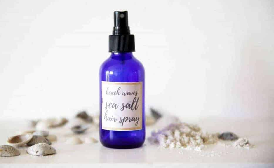 homemade sea salt hair spray in blue bottle surrounded by sea shells