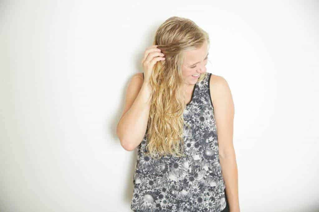 girl running fingers through freshly sprayed sea salt spray hair