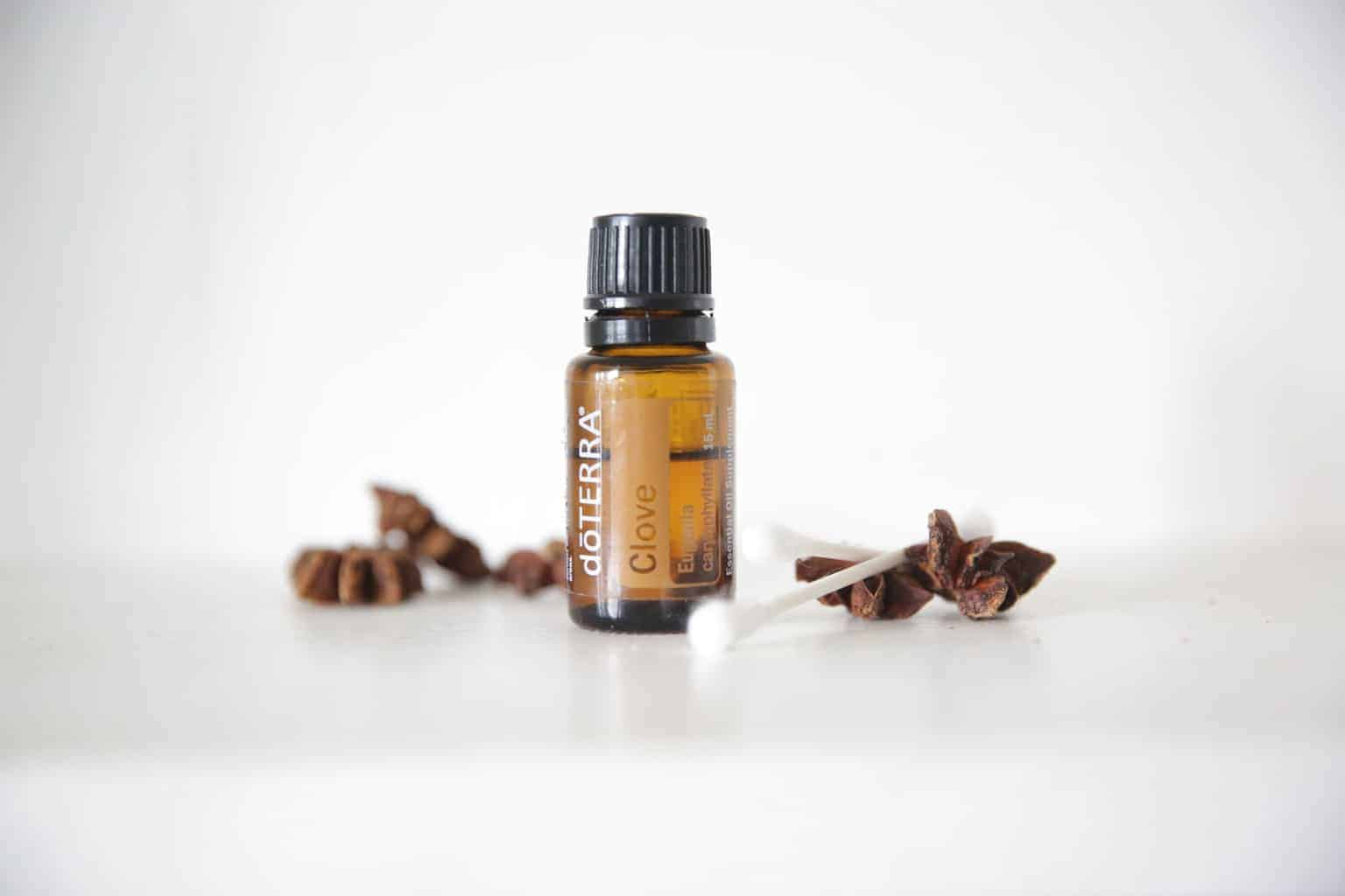 doTERRA clove essential oil bottle with dried cloves and a q tip