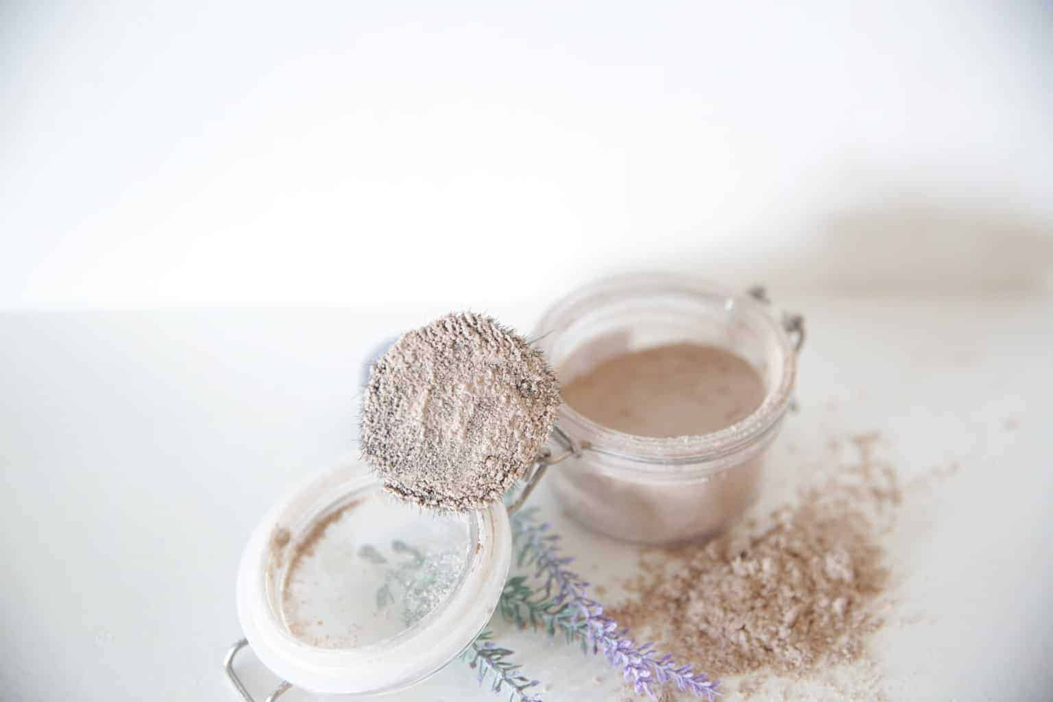 homemade dry shampoo powder in glass flip top container with lavender sprigs