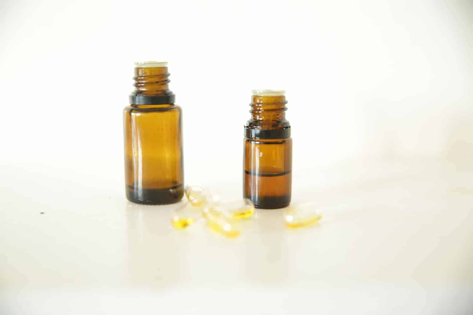 2 amber essential oil bottles with gel capsules on table