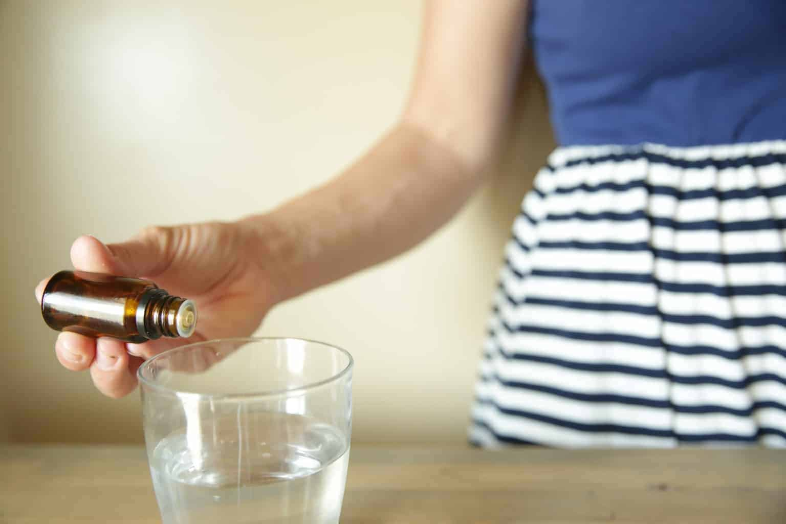 A women adding essential oils to water.