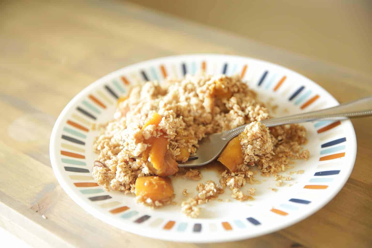 healthy peach crisp on small decorative plate
