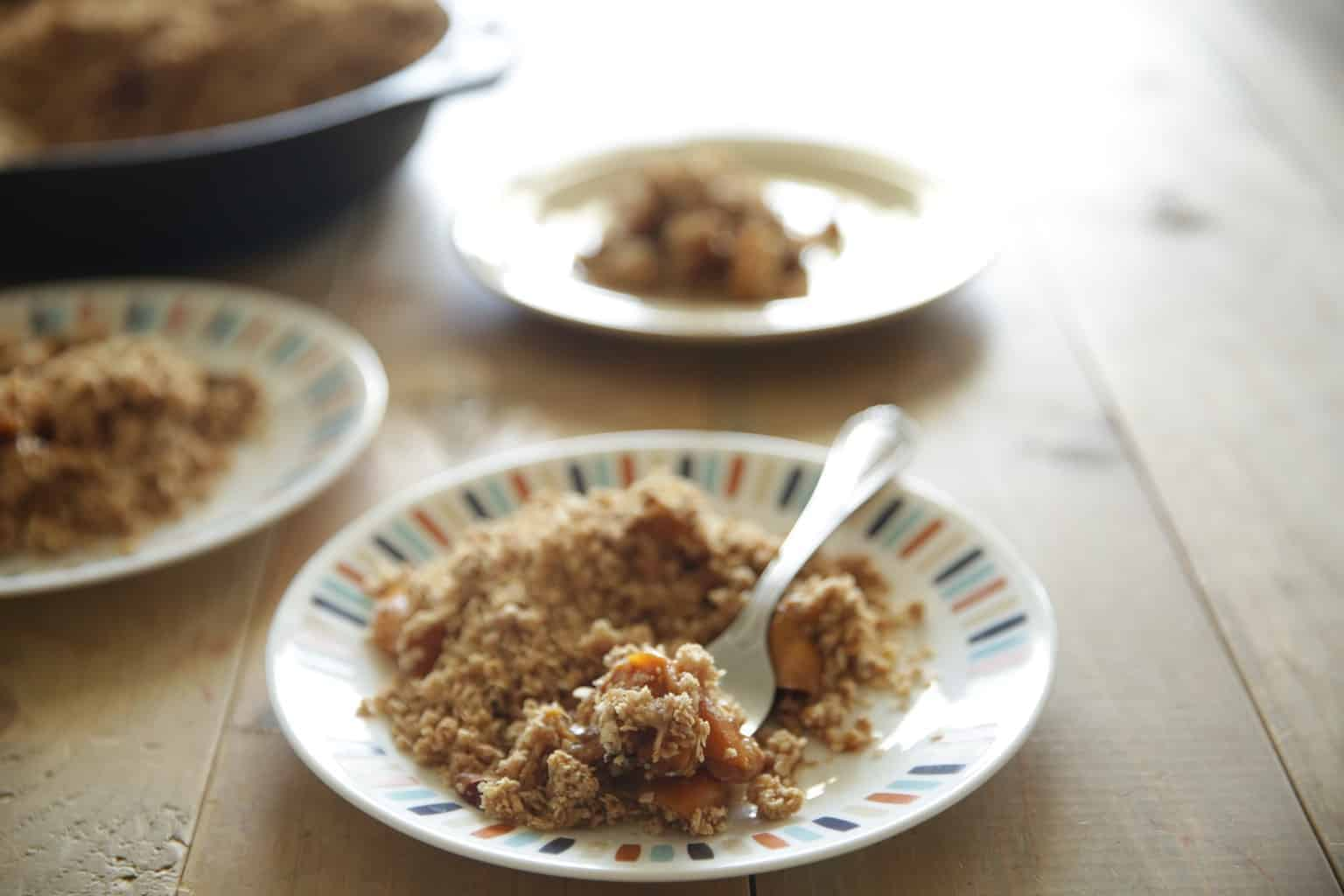 wooden table top with plates of peach crisp