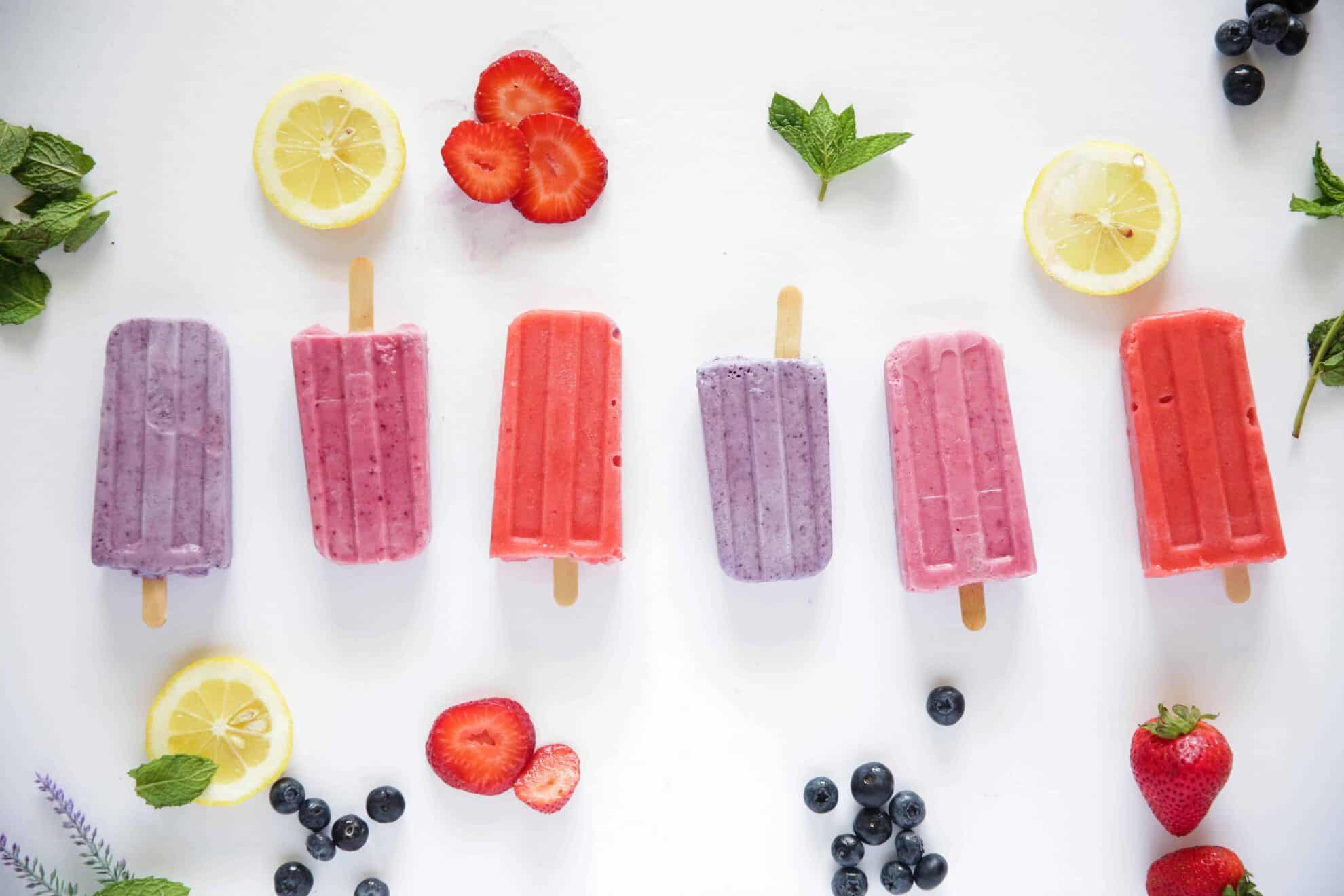 fruit and popsicles on white background