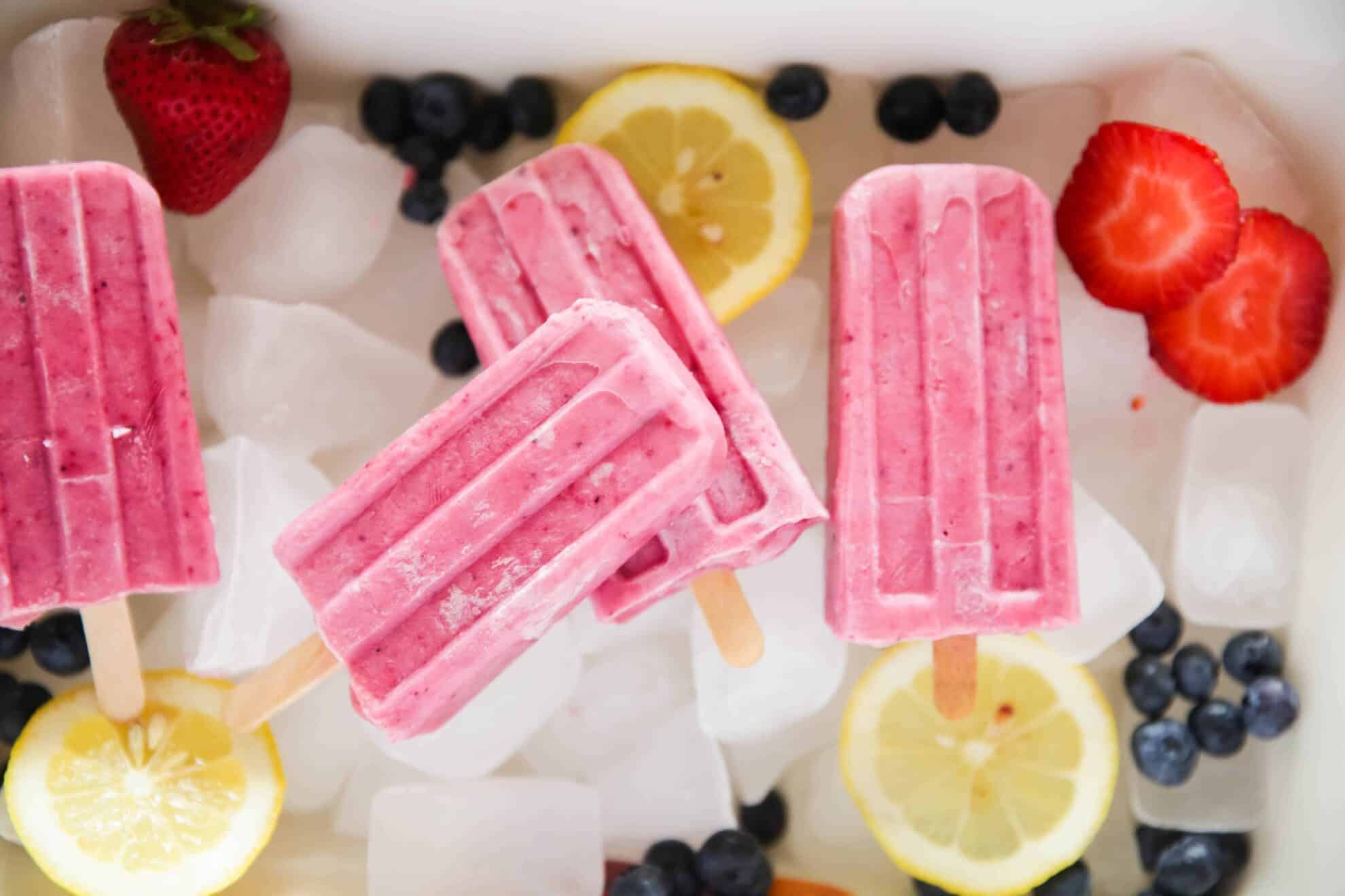 berries lemon slices and pink popsicles on ice