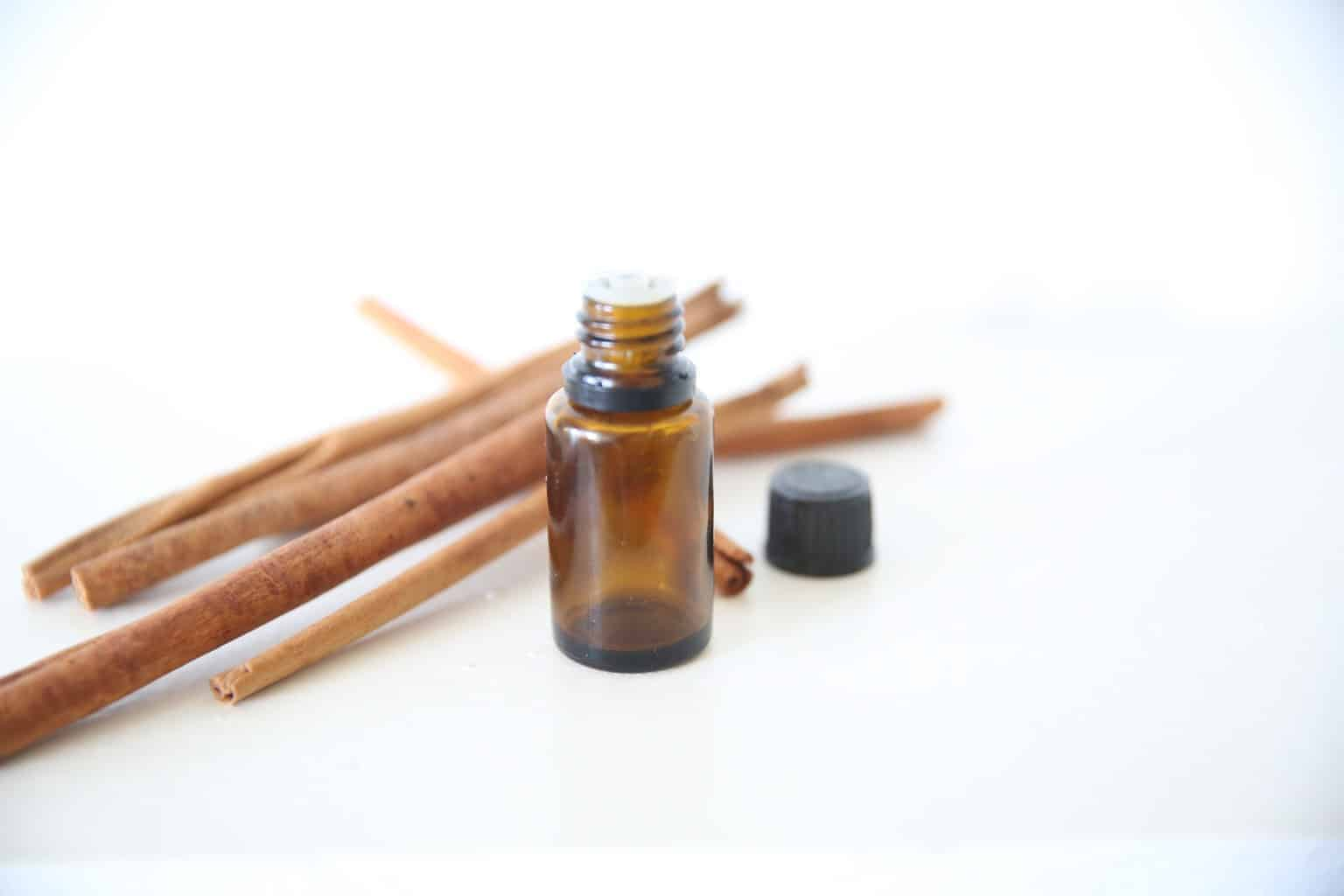 cinnamon essential oil bottle with cinnamon sticks on white marble