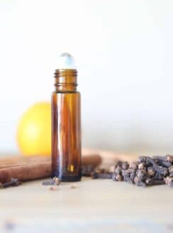 Cinnamon essential oils roller bottle with dried cinnamon.