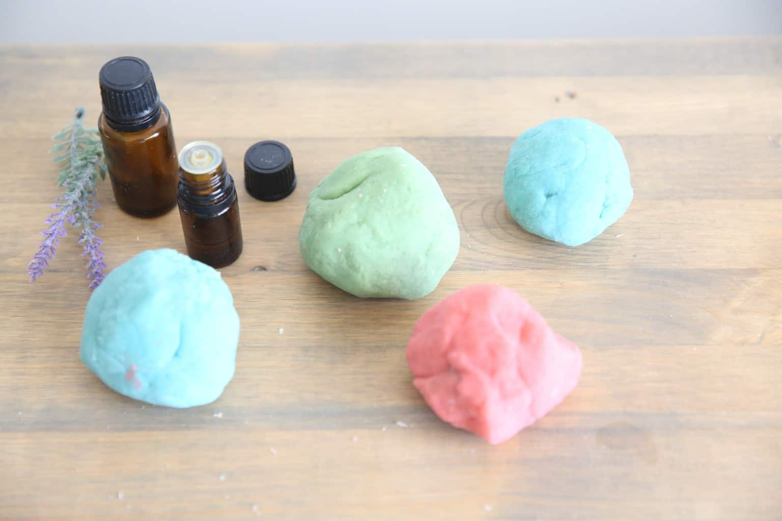 4 different colored balls of fresh made playdough on wooden table top