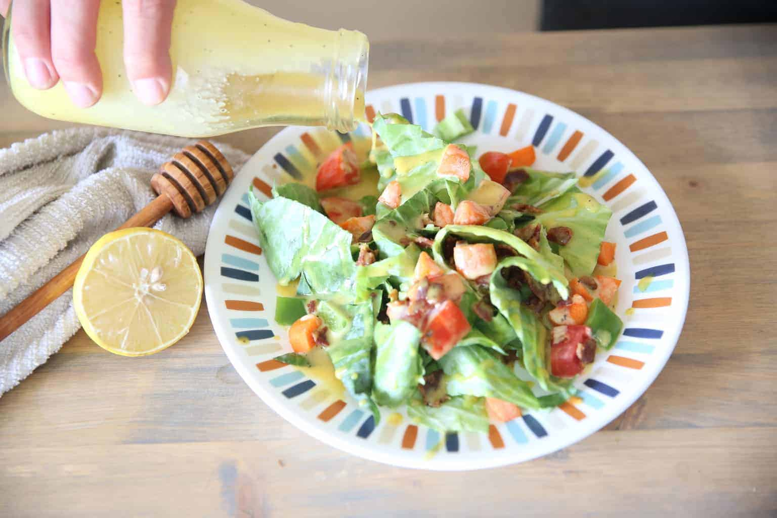 pouring homemade lemon honey mustard on salad from a glass jar