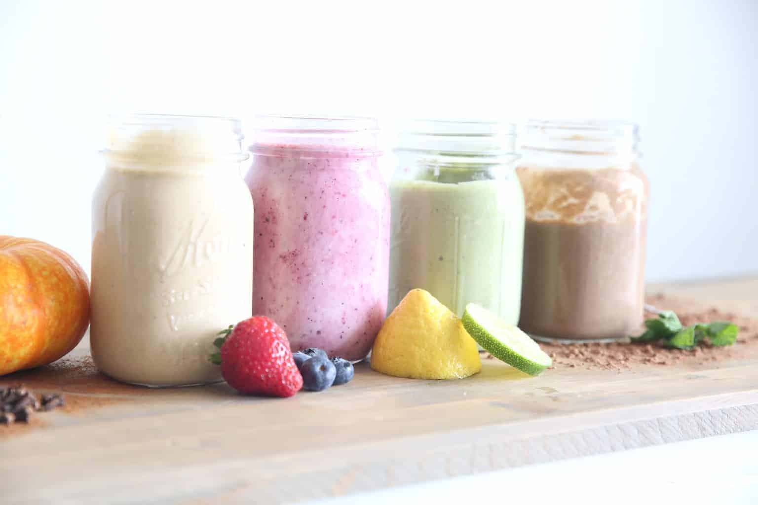 5 Healthy Smoothies with Essential Oils in 1 qt glass mason jars. fresh fruit laid around the base