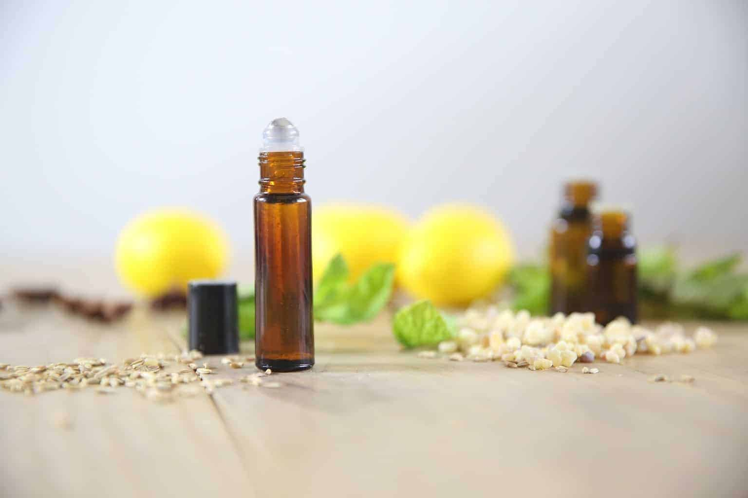 Essential oil roller bottle on wooden table with lemons in background.