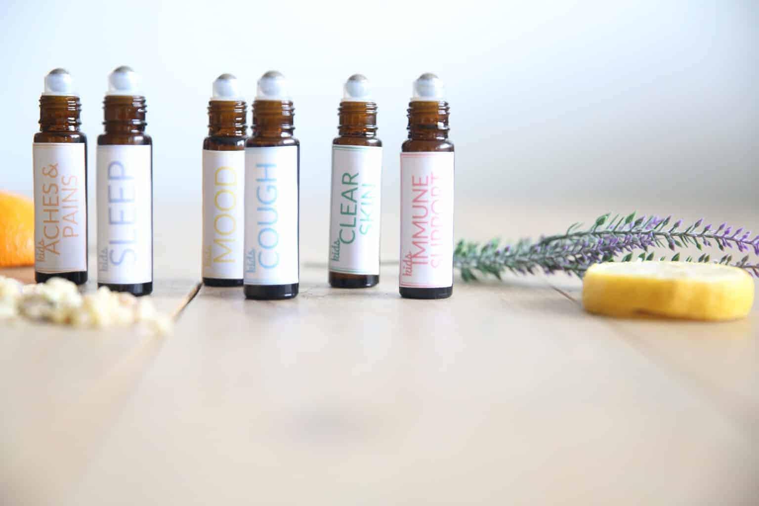 kids essential oils roller bottles on wooden table