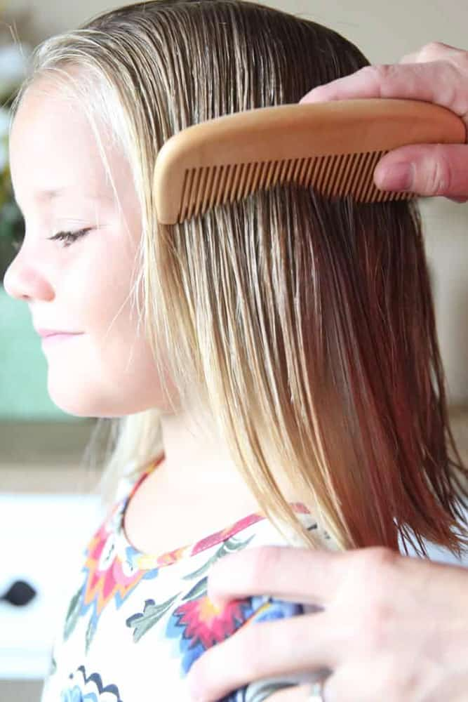 Wood comb combing through little girls hair.