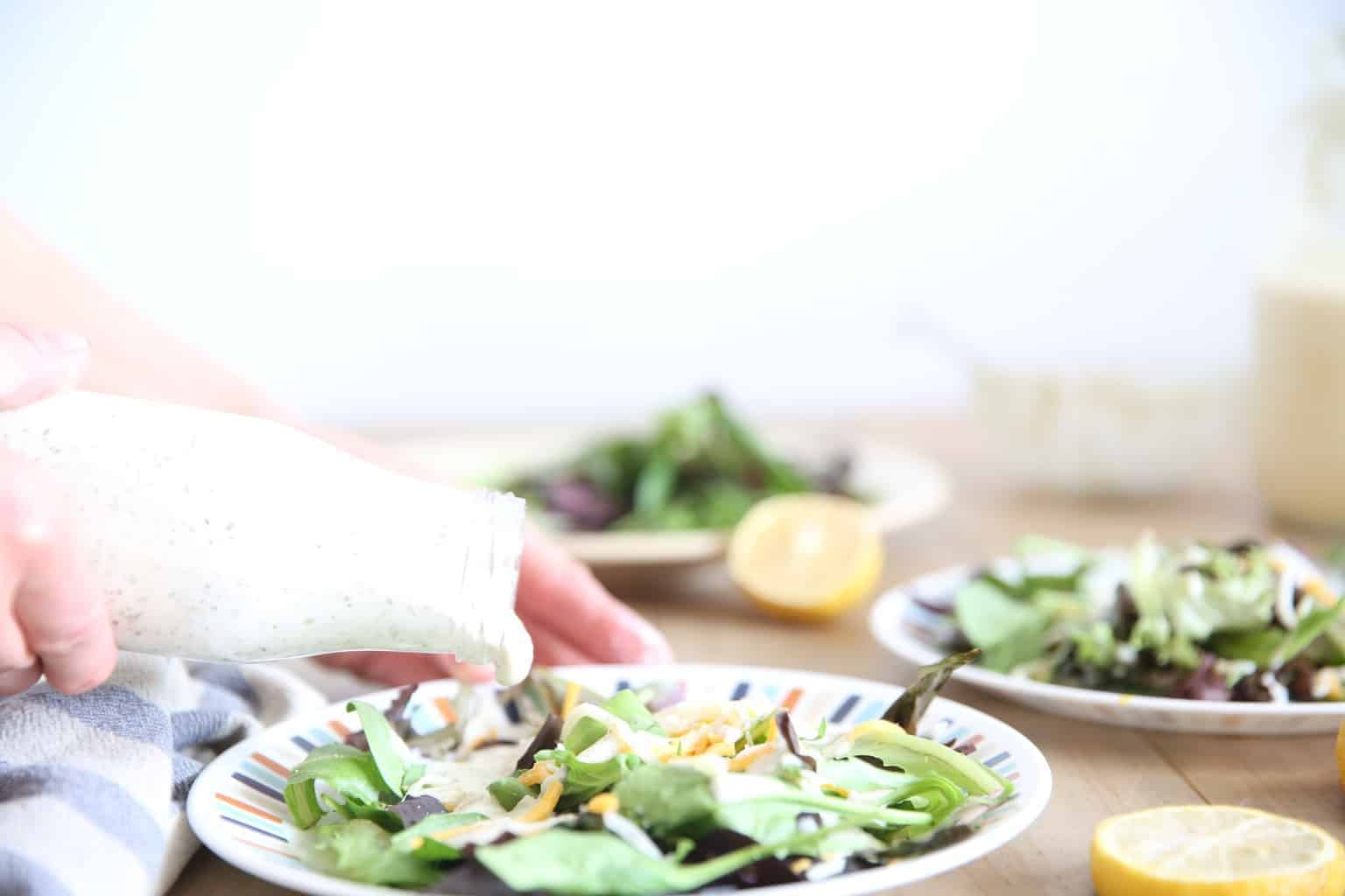 pouring homemade ranch dressing onto a small plate of salad