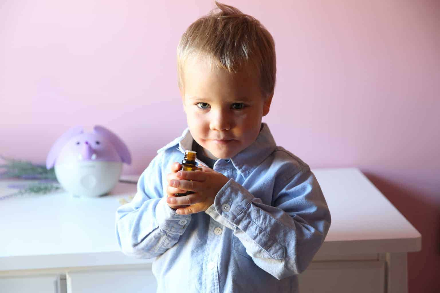 boy holding essential oil diffuser blend with lavender diffuser and white side table in background