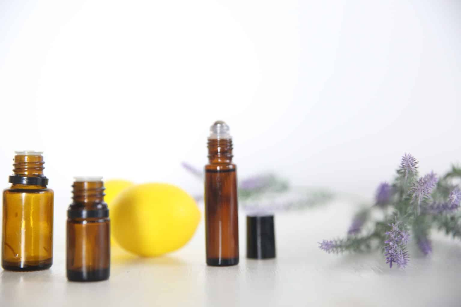 Roller bottles, fresh lemon, and lavender with white background.