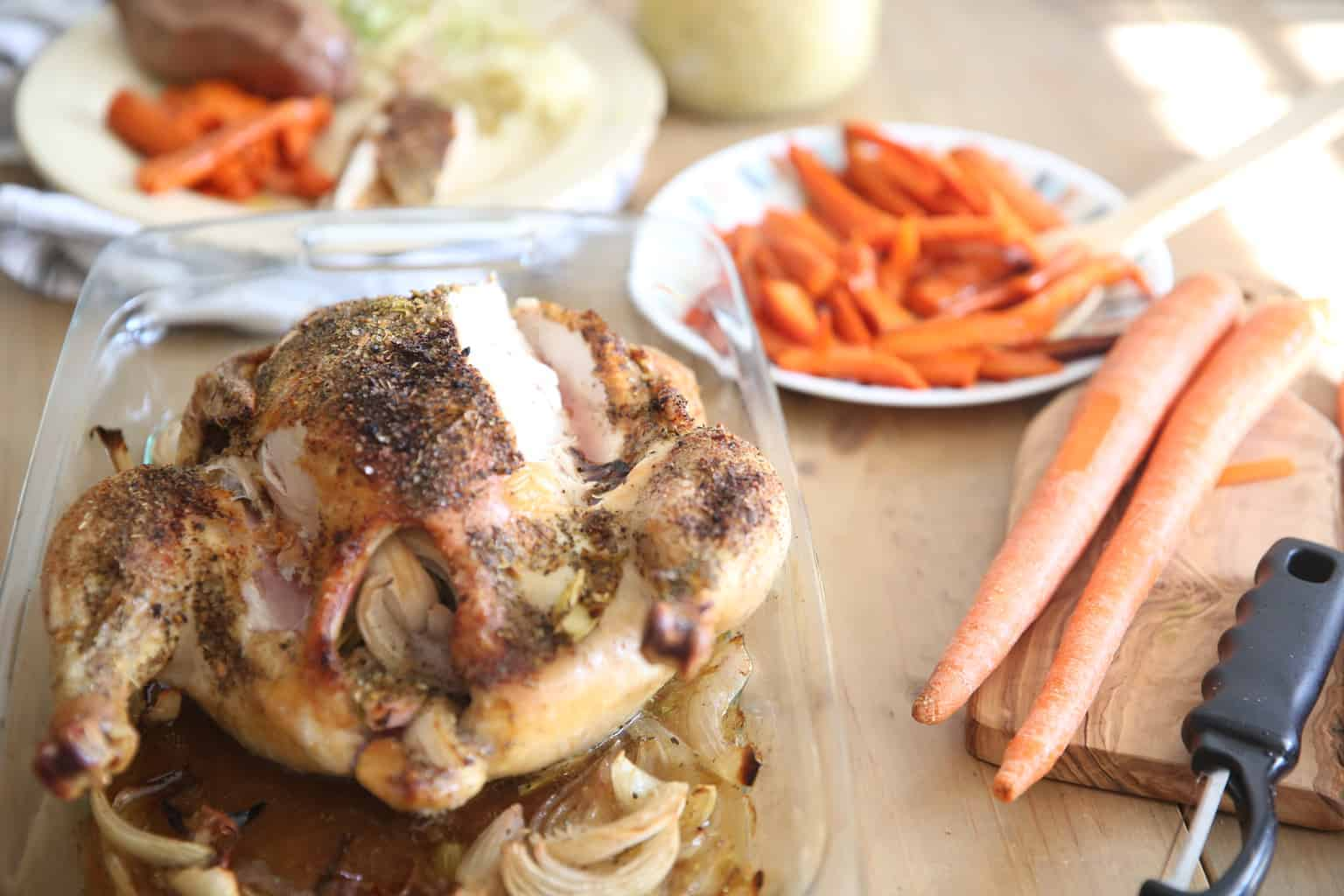 Roasted whole chicken and sliced carrots.