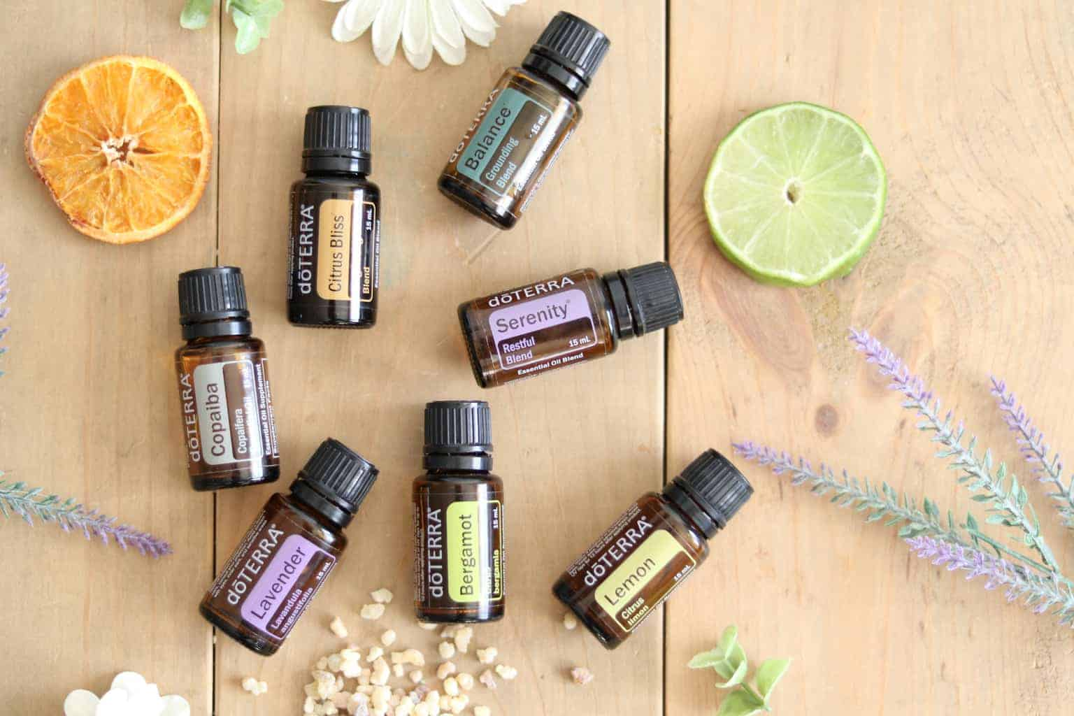 Essential oil roller bottles with dried flowers and fruits on wooden table.