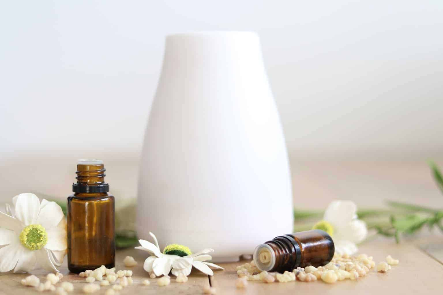 white essential oil diffuser surrounded by flowers and oil bottles on wooden table
