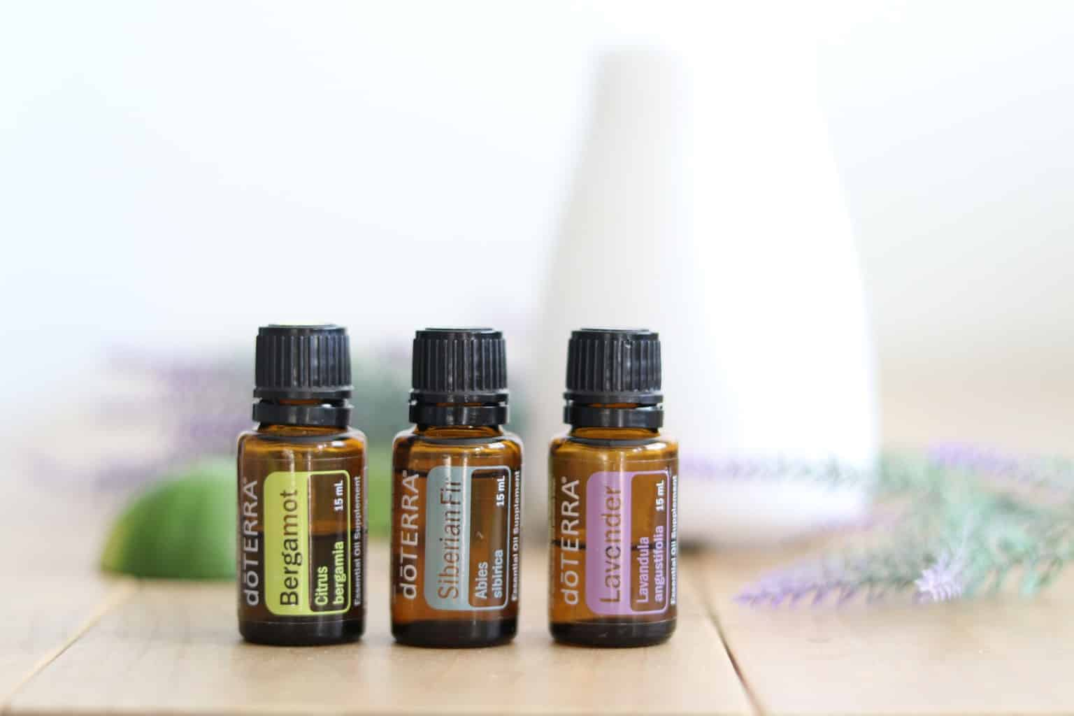 doTERRA roller bottles on table with diffuser in background.