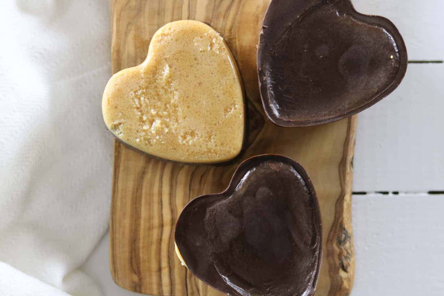 Paleo peanut butter chocolate hearts on white shiplap.