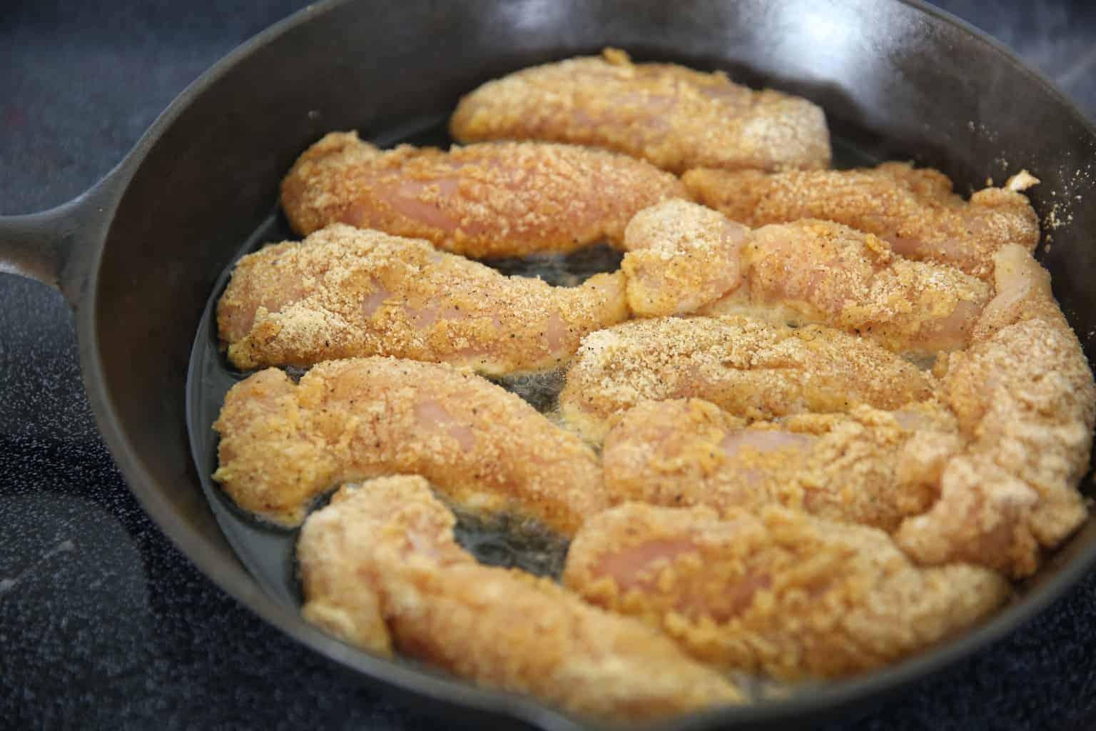 Frying chicken strips in cast iron skillet.