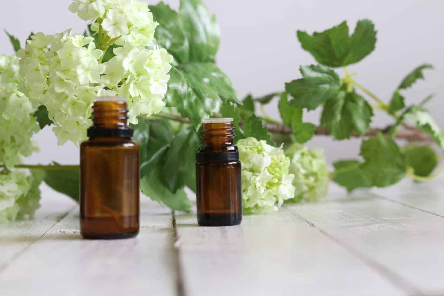 Essential oil bottles with fresh flowers in background.