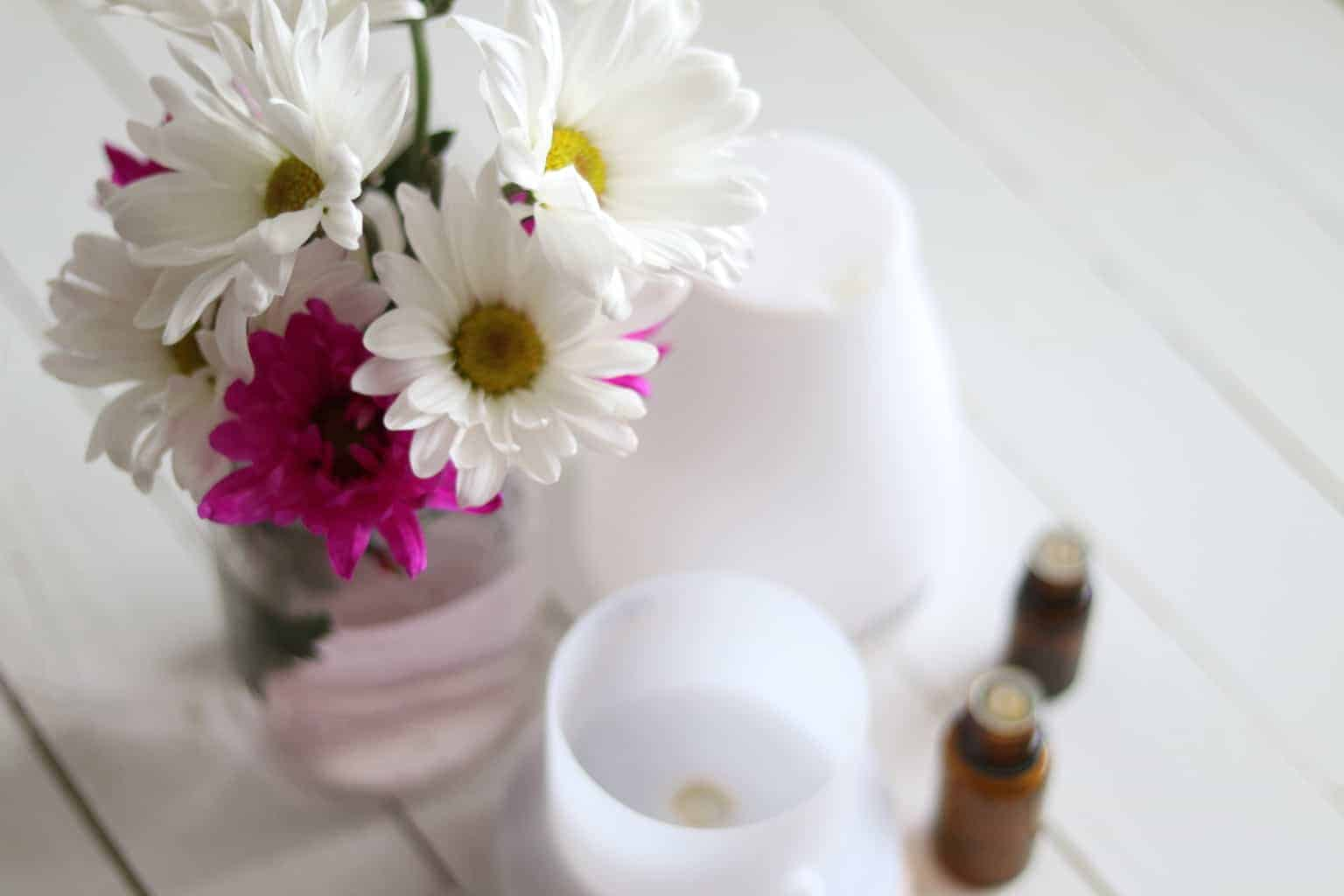 Fresh flowers in glass jar near essential oil bottles and oil diffuser.