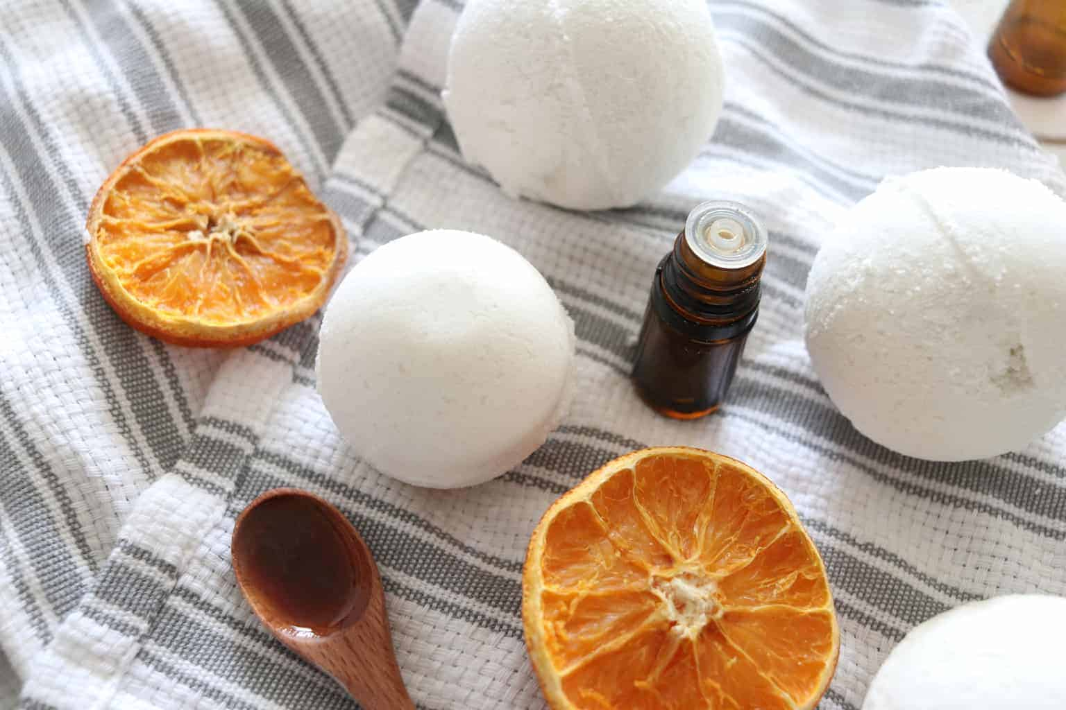 Bath bombs with dried orange slices and wooden tablespoon.