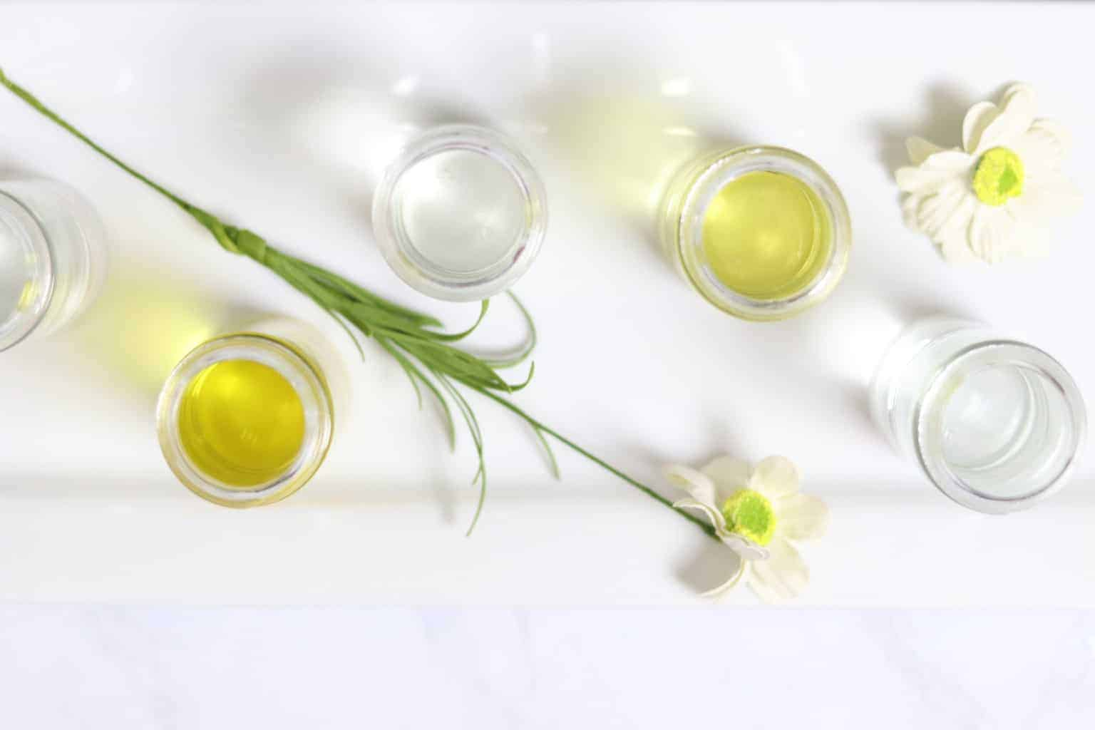Carrier oils in glass jars on white table with flowers around them.