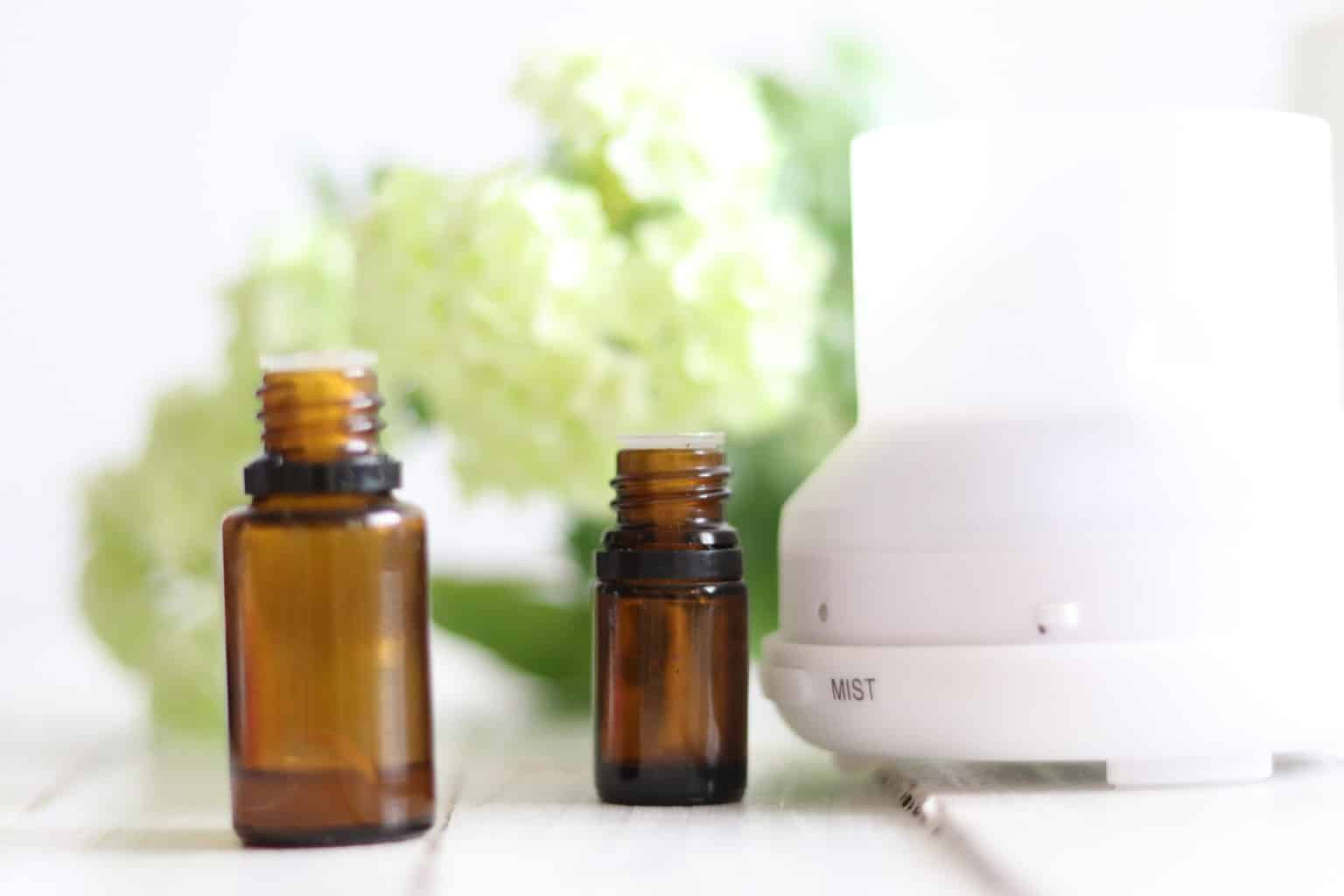 Essential oil bottles with flowers and oil diffuser in background.