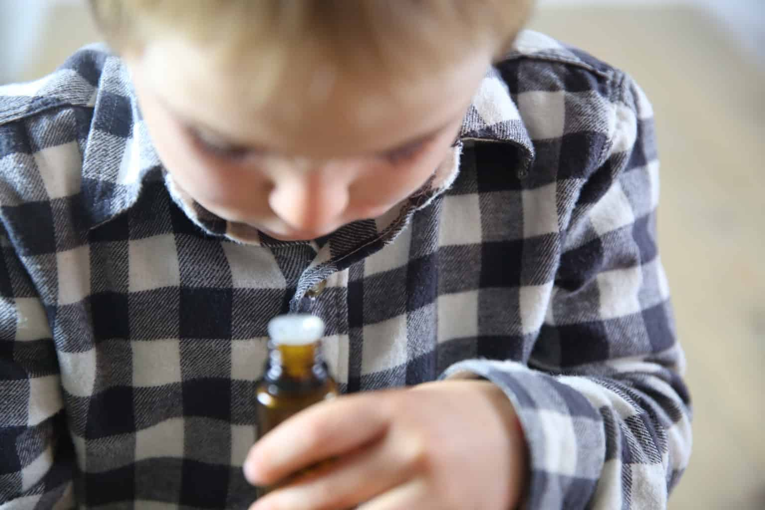 A little boy smelling essential oil from the bottle.