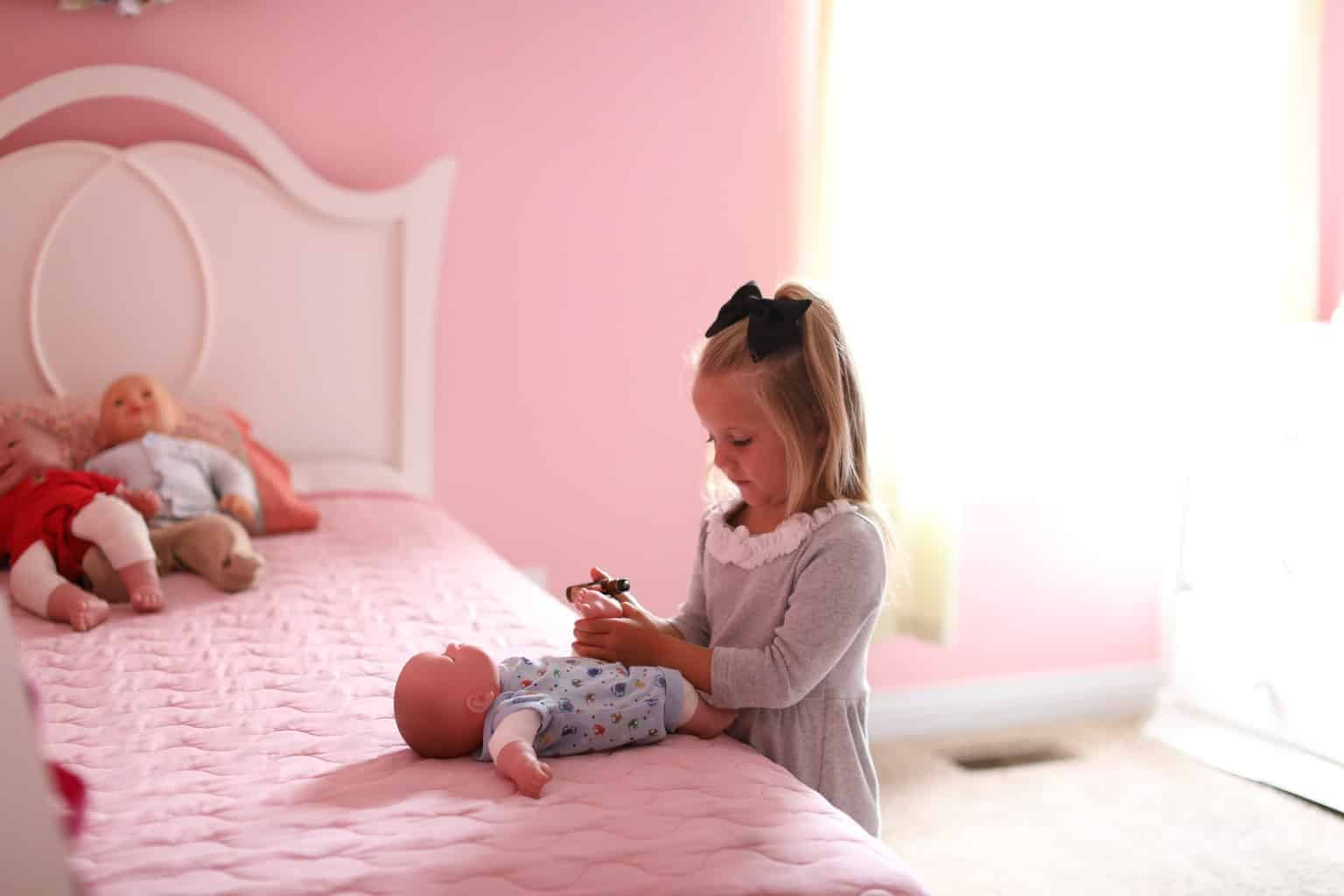 A little girl putting essential oil roller bottle on a plastic baby doll.