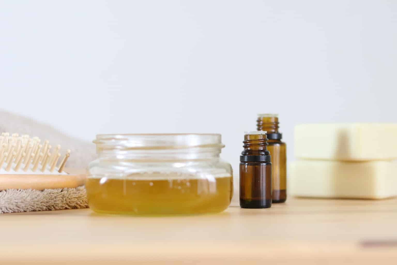 Homemade conditioner in mason jar and essential oil bottles on wooden table.