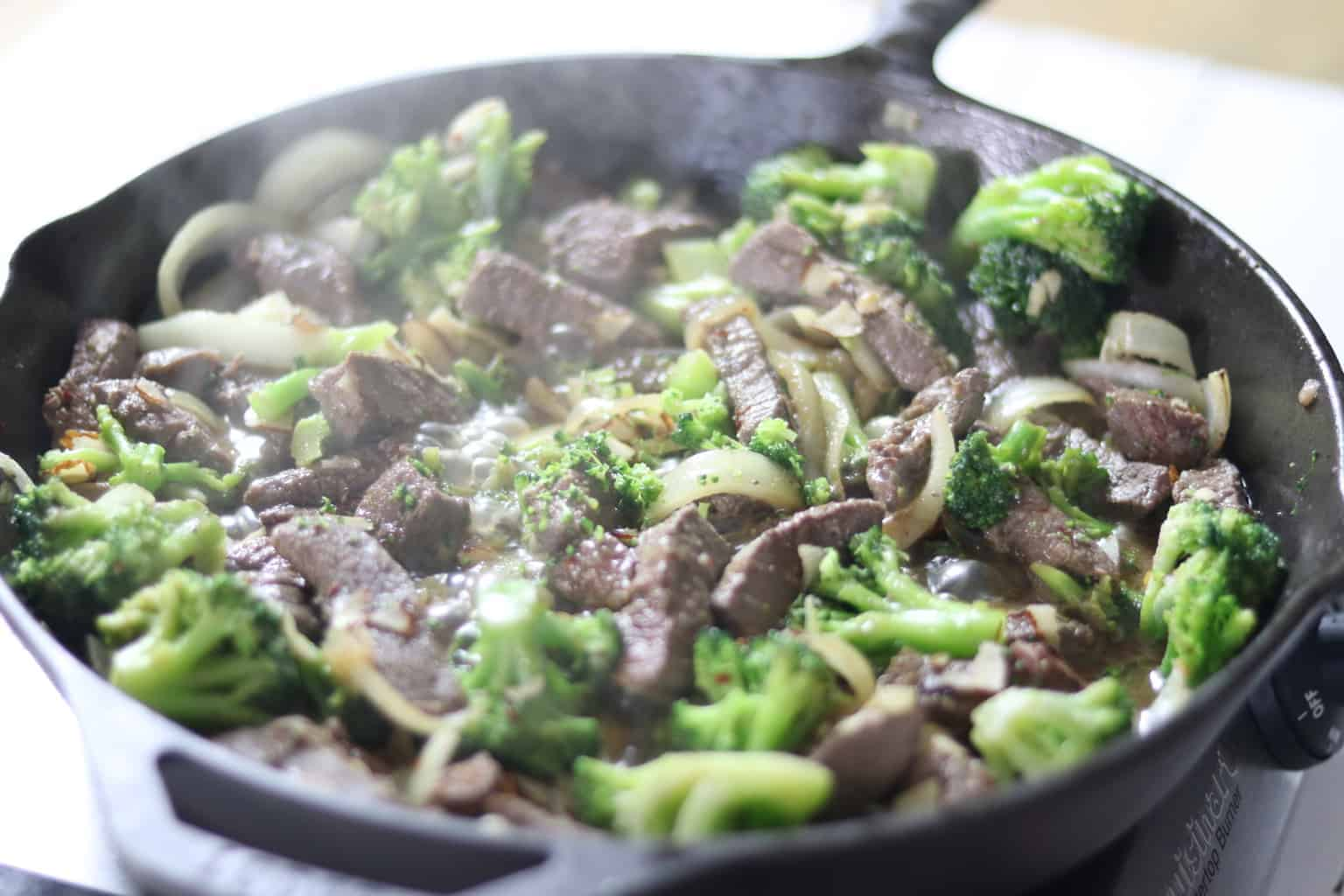 Broccoli, beef, and onions cooking in cast iron skillet.