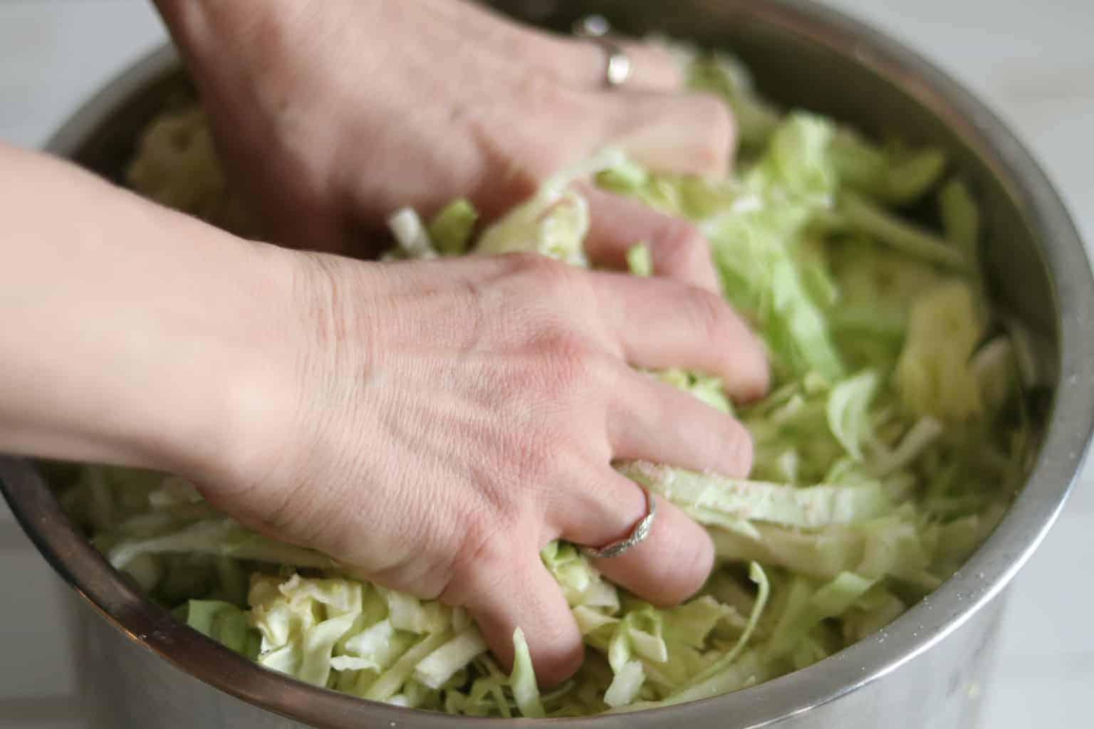 hands massaging cabbage to make brine