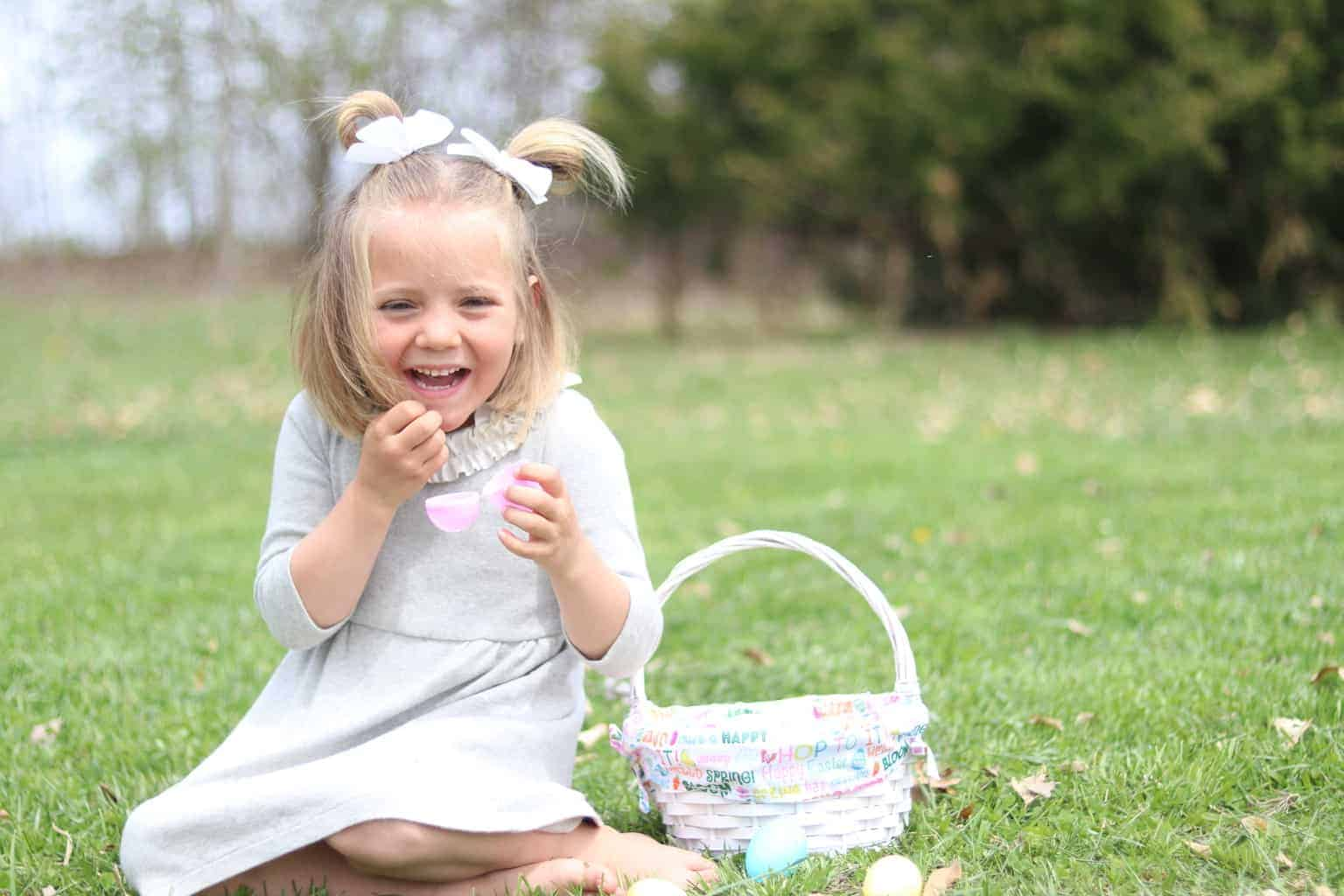Little girl sitting on grass with an Easter basket by her.