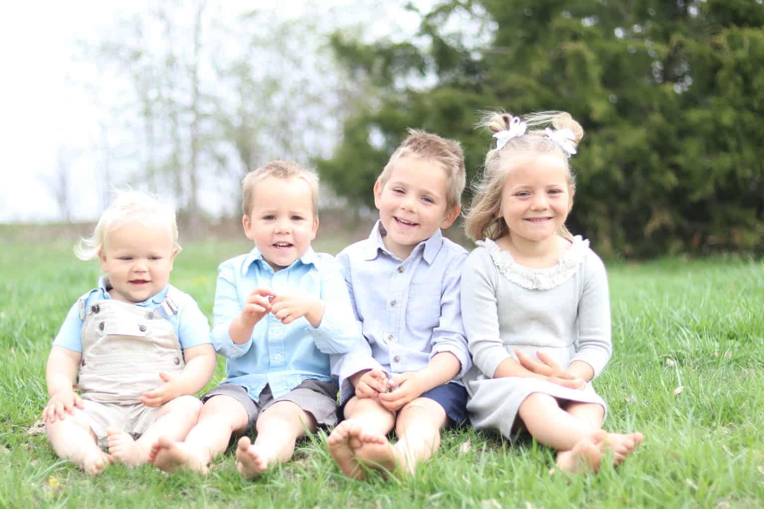 Four little children sitting on the grass.